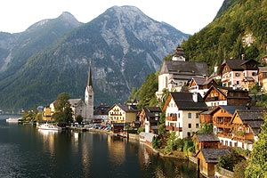 small European town by a lake with mountains in the background