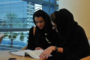 Photo of two women over a book