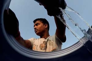 Man pumps water in India. Photo by Steve Elfers.