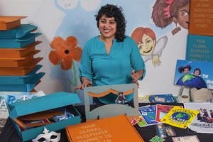 Geeta Raj holds an open children's book surrounded by children's books and toys in a playroom.