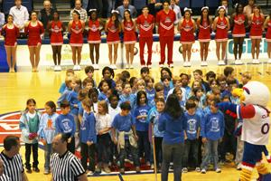 Janney Elementary students singing the national anthem at a basketball game.