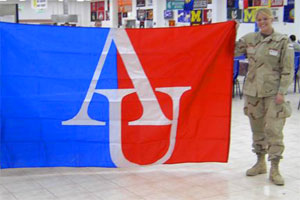 Alum Michelle Risinger with AU flag in Iraq