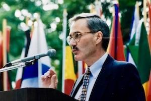 Professor Rodger Streitmatter speaks into a microphone in front of a series of flags