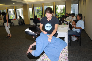 Woman giving a chair massage to another woman.