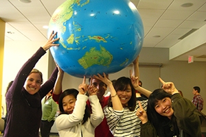 Students holding world globe.