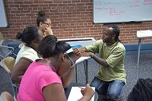 Photo: Babatunde Pyne works with students in SETH's POWER program.