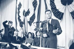 JFK stands behind a microphone and delivers a speech.