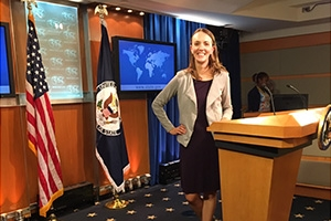 Journalism graduate student Shaun Conway Courtney stands at a podium in the State Department.