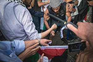Close-up of a pro-Palestinian group gathering around a man lighting a match while being recorded on a smart phone.