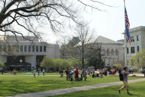 Photo of three buildings on the main campus Quad with students walking and lounging on the grass. The three buildings are the Bender Library, McKinley Hall, and Mary Graydon Center