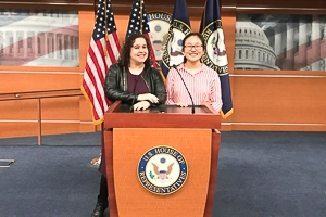 Tracy Hanqing and a friend post at a speaker's at the U.S. House of Representatives, flags on display close behind them.