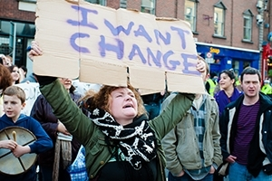 Woman holds up sign demanding change