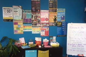The photo displays the entryway of the Wellness Center. Health-related posters are on the wall. A bookshelf contains sexual health resources.