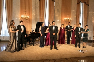Ten young people in formal wear stand in front of a piano
