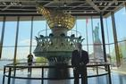 Professor Kraut stands in Statue of Liberty museum with windows behind him and torch too.