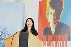 A dark-haired Caucasian woman stands at a podium in front of a bright Bob Dylan poster.
