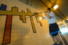An FSE participant cleans the tile mural in the Maine Avenue tunnel.