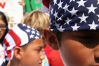 Children with US flag bandanas stand in a crowd