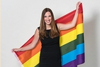 A photo of American University alumna Sarah McBride smiling in front of an LGBT rainbow flag.