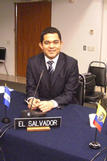 Walter Levia sitting in front of a sign for El Salvador at his internship