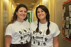 Amanda Riddle and Lauren Pesserini smile in Explore DC shirts as they discuss the program.