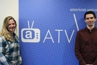 Abi Weaver (left) and Ben Fall (right pose in front of the ATV sign near ATV studios.