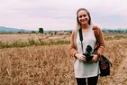 Erin McGoff standing in a field with a DSLR camera in Laos during her Alternative Break trip in the winter break of 2016-17.