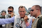 Former President George H. W. Bush on a Navy ship, speaking on the phone.