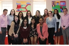 Students pose before colorful artwork at the Latin American Youth Center. Community-Based Research Scholars presented their research findings to the Latin American Youth Center.
