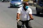 A man wearing a surgical face mask riding a bicycle on a road in Nigeria.