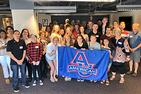 Students and parents with an AU banner at a summer send-off event