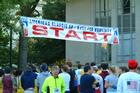 Runners socializing by starting line race banner