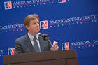 President Neil Kerwin gestures with his left hand while speaking at a podium in front of an AU backdrop
