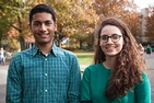 Thomas (male) stands on the left beside Filali (female), who wears glasses and a turquoise sweater. They are on the campus quad, with fall foliage in the background.