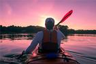Man kayaking on the Potomac River with sunset in front of him