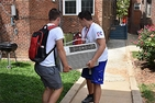 Two students carry an air conditioner unit into a building.