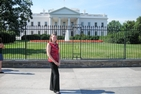 A young woman in a red flower-print blouse and black slacks poses in front of the White House.