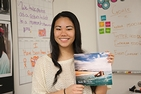Chua, with long dark hair, holds a copy of the her new photo book. The cover features a sunny beach scene.