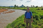 Carl LeVan stands in front of river, mountain, and valley in Africa.