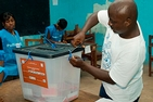 A Liberian election worker opens a ballot box.