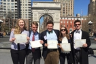 Five members of the American University Model United Nations team hold awards after NYU Model UN competition.