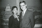 Sonya Gavankar and a male colleague stand in front of a Washington, DC backdrop on an American University Television set in 1999.