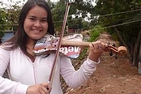 Girl holding violin made of recycled garbage