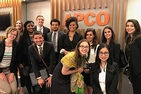 A group of students stand in front of an APCO sign during a site visit