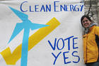 Student holding a sign promoting a ballot initiative on clean energy