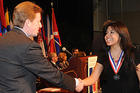 Photo of Claudia Soto Orozco receiving an award from American University President Neil Kerwin