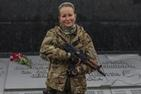 Ukrainian woman holding a rifle in military fatigues.