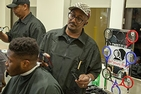 Student getting a haircut in barber chair.