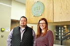 Chris Moody and Megan Litke posing at the ceremony recognizing Cassell Hall's LEED-silver certification. Moody and Litke are posing under the LEED decal.