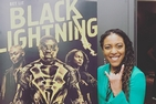 Alumna Anedra Edwards having fun and standing in front of a poster for the CW TV series that she works on, Black Lightning.